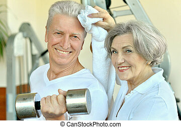 Couple in gym - Portrait of a senior couple exercising in...