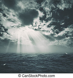 wild storm on the sea with sun beam from the cloudy skies