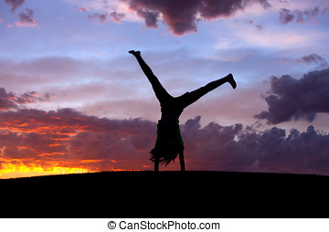 Cartwheel at sunset - A girl does a cartwheel at sunset on...