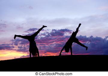 Kids doing cartwheels. - A boy and girl do cartwheels...
