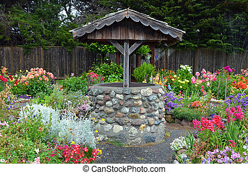 Wishing well in dahlia garden - Old brick wishing well in...
