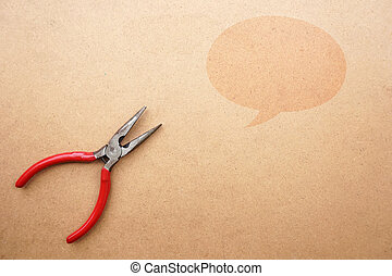 Red pliers on wooden background with space for text