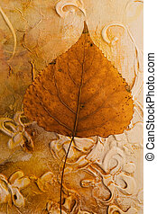 pressed leaf in front of artwork, artwork in the back is...