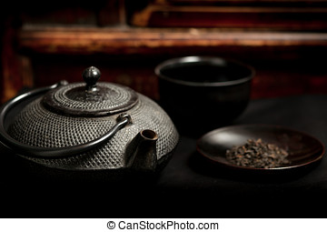 Japanese iron teapot and heap of tea leaves before mahogany...
