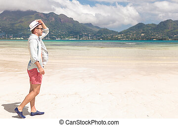 side view of a young man walking on the beach