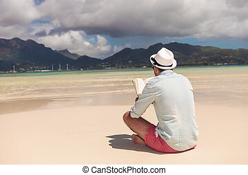 young man reading a book on the beach