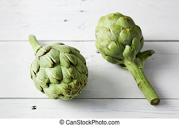 Artichokes - Close up of two artichokes on a white wooden...