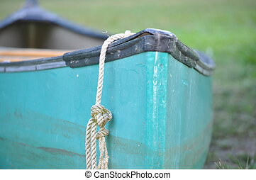 Canoe Front - A green canoe on the grass with a rope hanging...