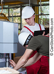 Man demonstrating factory machine to inspector - Vertical...