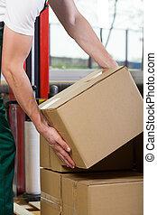 Foreman's hands lifting box at storehouse - Close-up of a...