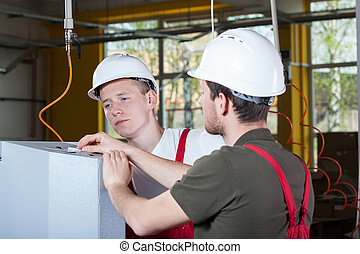 Two specialists repairing factory machine