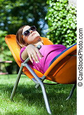 Woman relaxing in a garden on a sunbed