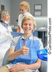 Teenager patient thumbup at dental surgery dentist and nurse...