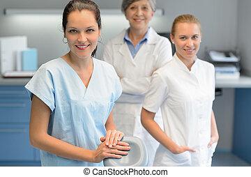Three dentist woman team at dental surgery looking camera...