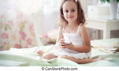 Little girl in white dress with mobile phone FullHD video