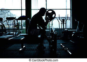 silhouette of an athletic man working out at gym Fitness...