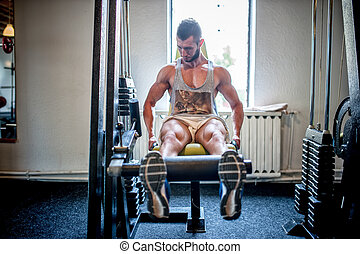 bodybuilder working out and training at the gym, legs and...