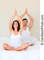 Couple sitting on bed in meditation pose - Young couple...