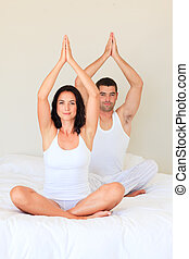 Couple doing yoga in bed