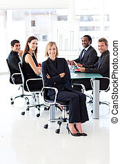 Business team smiling at the camera in an office -...
