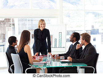 Businesswoman smiling at her colleagues in a meeting -...