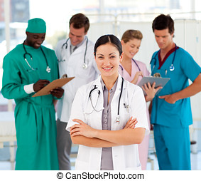 Attractive female doctor with her team in the background
