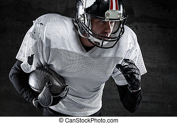 american football player holding a ball and running -...