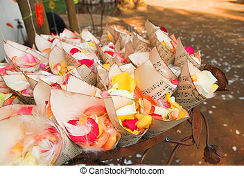 A flower and feather confetti with red, pink and yellow rose...