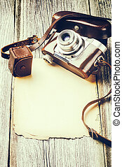 Retro camera on old wood background with vintage paper
