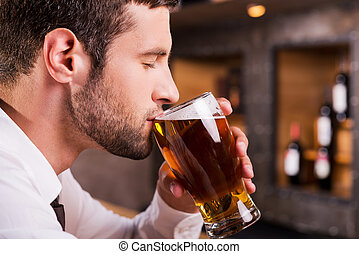 Man drinking beer Side view of handsome young man drinking...
