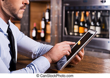 Surfing web in bar. Close-up of man in shirt and tie working...