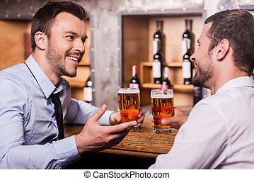 Friday night fun. Two cheerful young men in shirt and tie talking to each other and gesturing while drinking beer at the bar counter