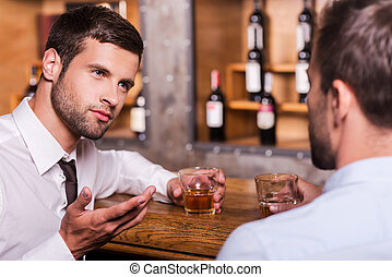 Spending night in bar. Two confident young men in shirt and tie talking to each other and gesturing while drinking whisky at the bar counter