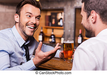 Spending Friday night in bar. Two happy young men in shirt and tie talking to each other and gesturing while drinking beer at the bar counter