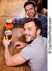 Friends in bar Top view of two happy young men drinking beer...