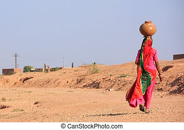 Local woman carrying jar with water on her head, Khichan...
