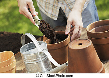 Potting - Hands putting soil in clay pot with a small shovel