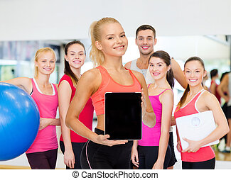 smiling woman showing tablet pc blank screen - fitness,...