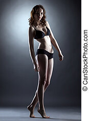 Fascinating leggy girl posing in studio, on gray backdrop