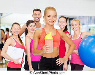 smiling sporty woman with protein shake bottle - sport,...