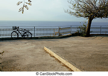 bicycle on embankment at sea, garden with nobody at morning