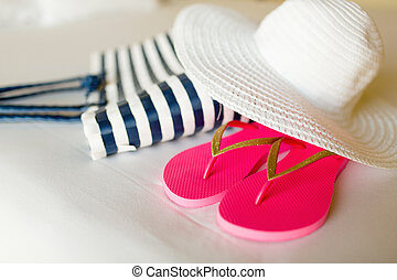 close-up of beach bag, hat and flip-flops on bed - vacation,...