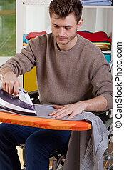 Disabled man ironing shirts at home - Capable disabled man...