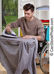 Disabled ironing shirts on board - Disabled man ironing...