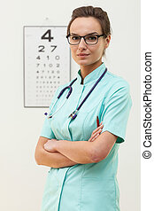 Confident female optometrist standing with arms crossed -...