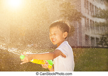 Cheerful little boy playing water guns in the park