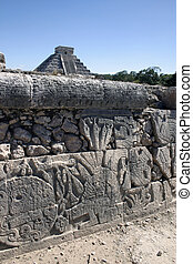 Maya hieroglyphs with the great pyramid in the background Kukulc