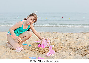 Happy little girl on the beach - Happy little girl playing...