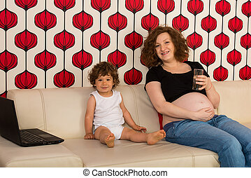 Pregnant mom and toddler boy home sitting togheter on couch
