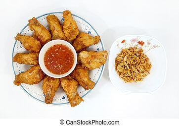 ied chicken legs with fried garlic on wihte